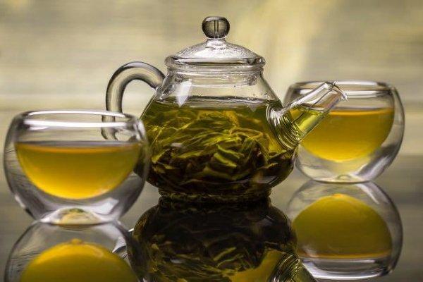 Зеленый чай в стеклянном чайнике и двух стеклянных пиалах